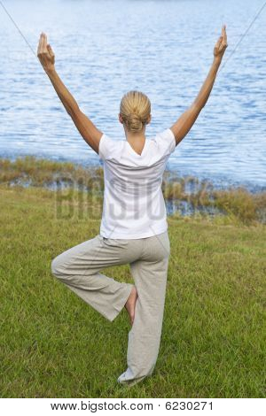 Beautiful Young Woman Practicing Yoga By A Tranquil Blue Lake