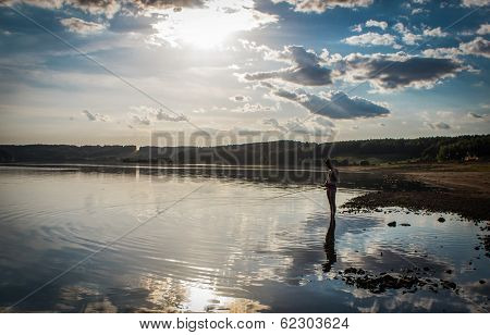 lone fisherman on the lake at sunset