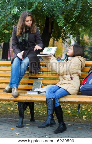 Two Young Girls Reading In The Park.