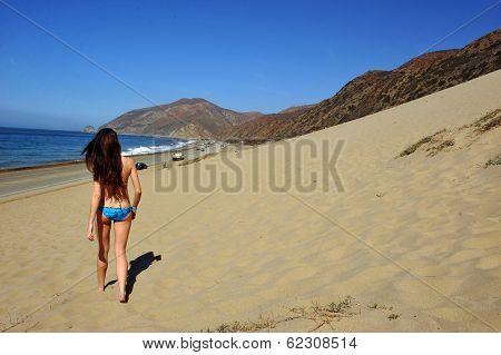 Bikini Model walking on sand dues