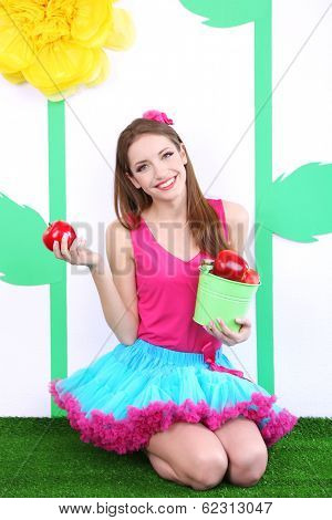 Beautiful young woman in petty skirt holding bucket of apples on decorative background