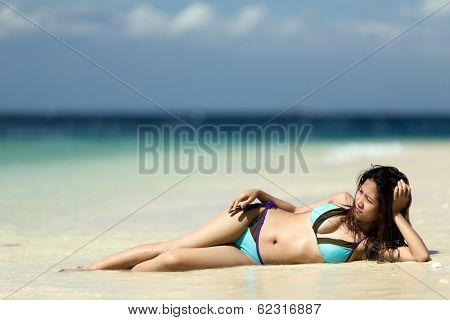 Filipina woman lying on the seashore