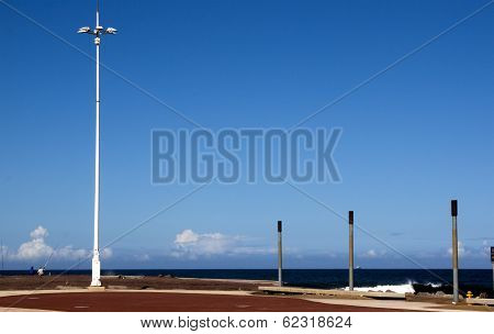 Fishermen And Lightpole On Pier At Beach