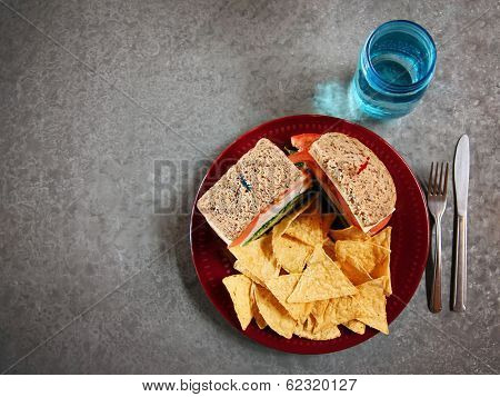 a well balanced healthy diet of a turkey sandwich with tortilla chips and a glass of water in a nice restaurant
