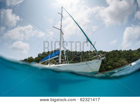 Split shot of the sail boat anchored near the green island at sunny day