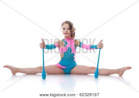 Cute gymnast posing sitting on splits with mace