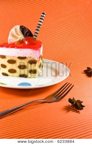 Tasty And Colorful Multy Layer Cake With Chocolate Decorations And Red Jelly.
