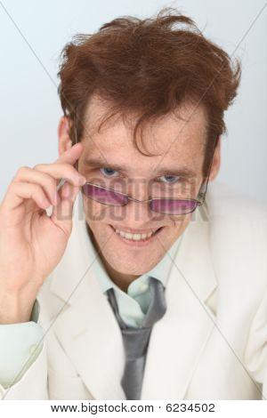 Cheerful Tousled Guy Looks Over Eyeglasses