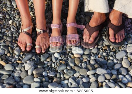 lot of feet on the stones. family with girl