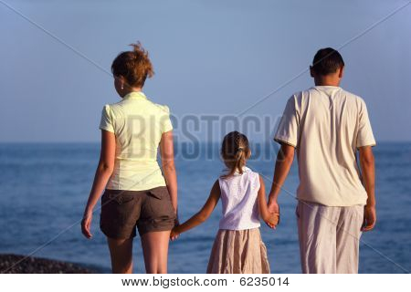 Family with girl walks along sea beach. Back view.
