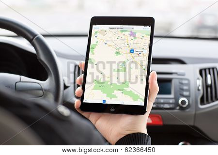 Man Sitting In The Car And Holding A Mini Ipad With Apple Maps On The Screen