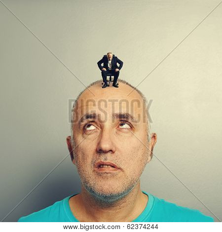 tired senior man looking up at small angry businessman on his head
