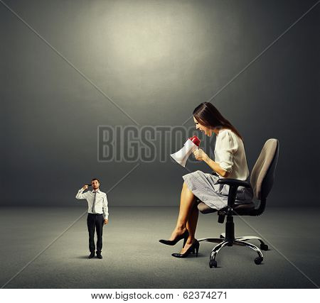 dissatisfied businesswoman and small man with gun over dark background