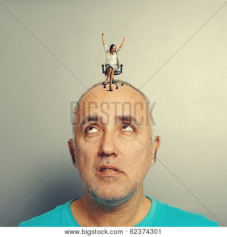 displeased man looking at happy young woman on his head