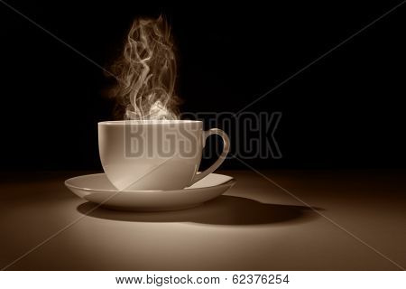 Hot coffee or tea in a cup silhouette against a dark background