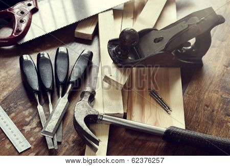 Old antique woodworking or carpentry tools on a hardwood floor concept for construction or repairing