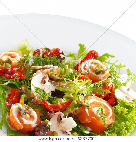 Fresh delicious salmon rolls with cream cheese on lettuce with button mushrooms on a round plate isolated on white.