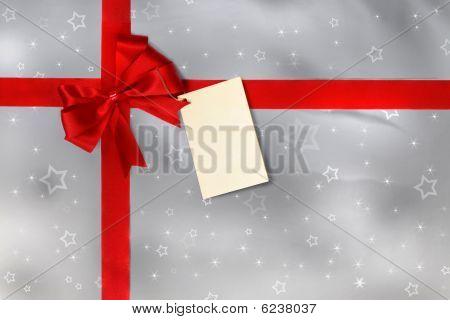 Presente com fita vermelha, arco e tag