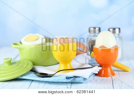 Boiled eggs in pan and eggcup on color wooden table, on light background