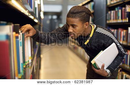 Young Student Looking For Reference Books At University Library