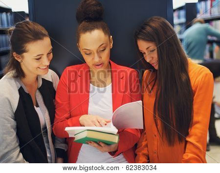 Young Female Students Sharing A Book In Library