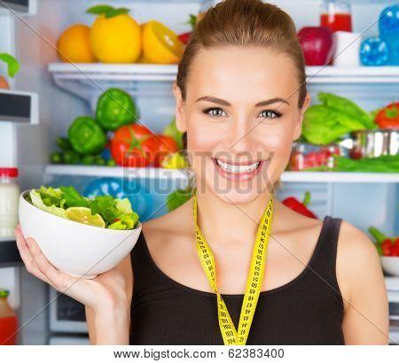 Closeup portrait of cute smiling woman with measure tape and fresh vegetables salad, sportive trainer, organic food, health and beauty care concept