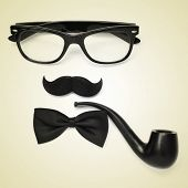 a pair of glasses, a mustache, a bowtie and a smoking pipe on a beige background depicting a gentlem