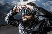stock photo of biker  - biker with black leather jacket and old glasses - JPG