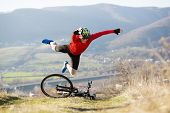 foto of biker  - Mountain Biker has a painful looking crash with his bike - JPG