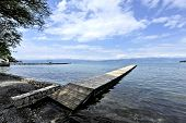 picture of dock a lake  - A long and a thin dock in the shore of Lake Ohrid. Clouds in the sky on a sunny day. A shadow of a tree is laid over the beginning of the dock, and the Sun is shining on the part that stretches to the lake.