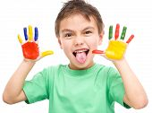 picture of sticking out tongue  - Portrait of a cute cheerful boy showing his hands painted in bright colors and sticking out tongue - JPG