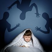 stock photo of boys night out  - boy under the covers with a flashlight the night afraid of ghosts - JPG