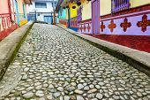 stock photo of cobblestone  - Colorful cobblestone street in town of Guatape in Antioquia Colombia - JPG