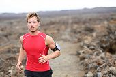 Man running - trail runner cross country training outdoors for marathon or triathlon ironman. Handso