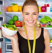 picture of sportive  - Closeup portrait of beautiful cheerful girl holding in hand bowl with fresh tasty green salad - JPG
