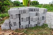 stock photo of cinder block  - Neat stack of concrete blocks and bricks for construction of tile sidewalk - JPG