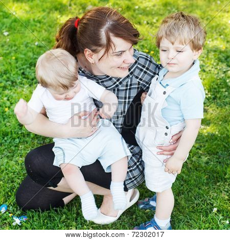Happy Caucasian Family Of Three: Young Mother And Two Little Sib
