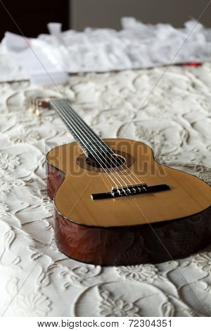 Spanish classical guitar lying on the bed