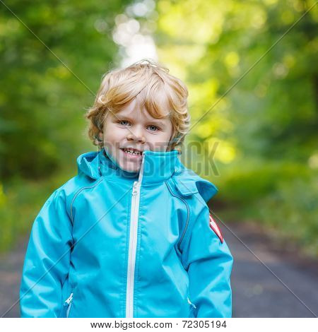 Portrait Of Blond Little Toddler  Boy In Blue Waterproof Raincoat In Autumn Forest