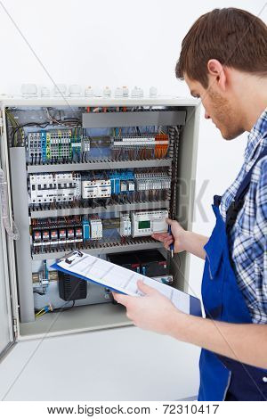 Technician Holding Clipboard While Examining Fusebox