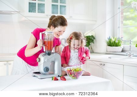 Pretty Laughing Toddler Girl And Her Beautiful Young Mother Making Fresh Strawberry And Other Fruit