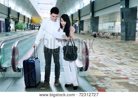 Young Couple Standing In Airport