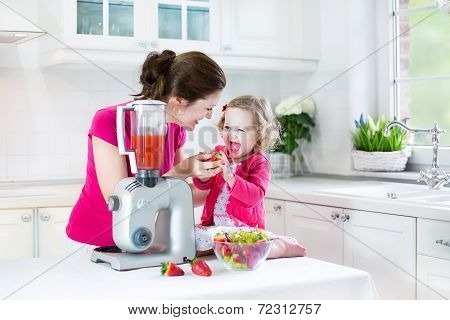 Happy Laughing Toddler Girl And Her Beautiful Young Mother Making Fresh Strawberry And Other Fruit
