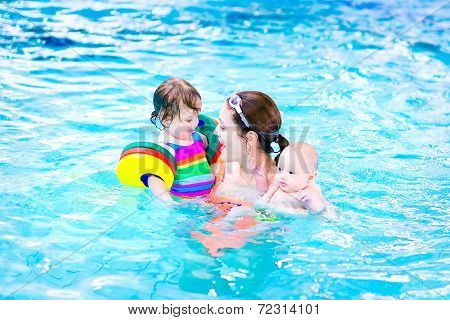 Young Mother Having Fun In A Swimming Pool With A Toddler Girl And Baby Boy