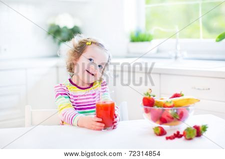 Sweet Toddler Girl having breakfast drinking juice and eating corn flakes with strawberry