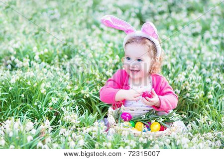 Adorable Toddler Girl Wearing Bunny Ears Playing With Easter Eggs In A White Basket Sitting