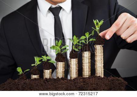 Businessman Stacking Saplings On Coins Representing Growth