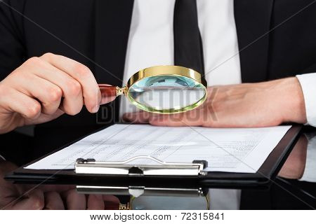 Businessman Analyzing Document With Magnifying Glass At Desk