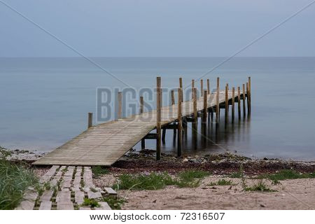 Wooden Pier On Beach In A Gloomy Predawn