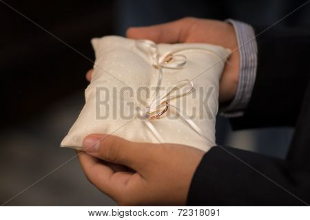 Best Man Holding Wedding Rings On The White Silk Pillow.